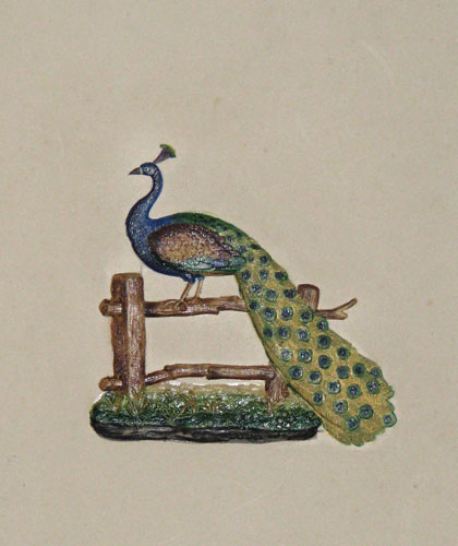 [A peacock standing on a fence.]